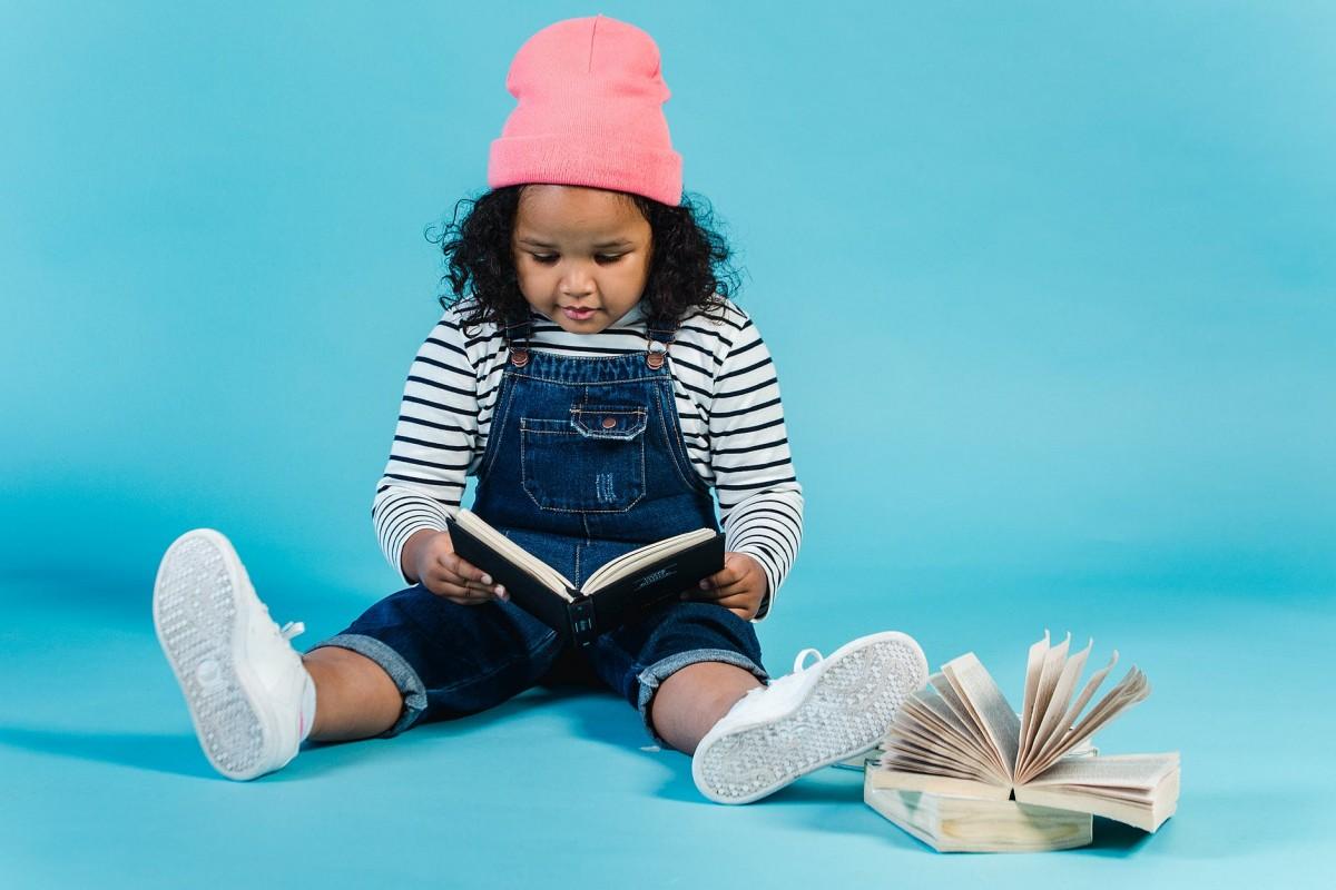 adorable black girl reading interesting book